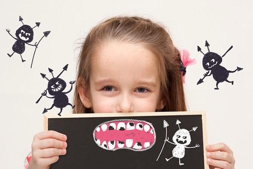 むし歯のイラストをもつ女の子
